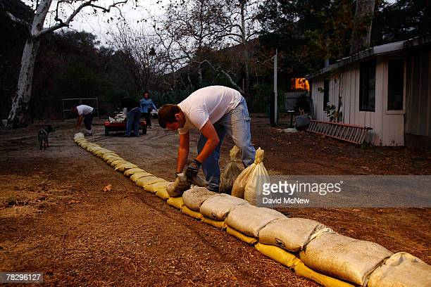 Residents of Modjeska Canyon build a wall of sandbags in preparation for the arrival of a storm that could bring flash floods debris flows and mud...