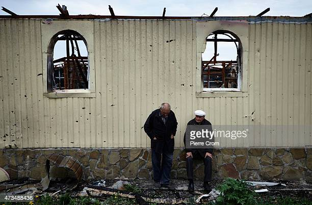 Residents of Nikishyne sit in the remains of a building on May 15 2015 in Nikishyne Ukraine 300 of the 800 residents of Nikishyne returned to the...