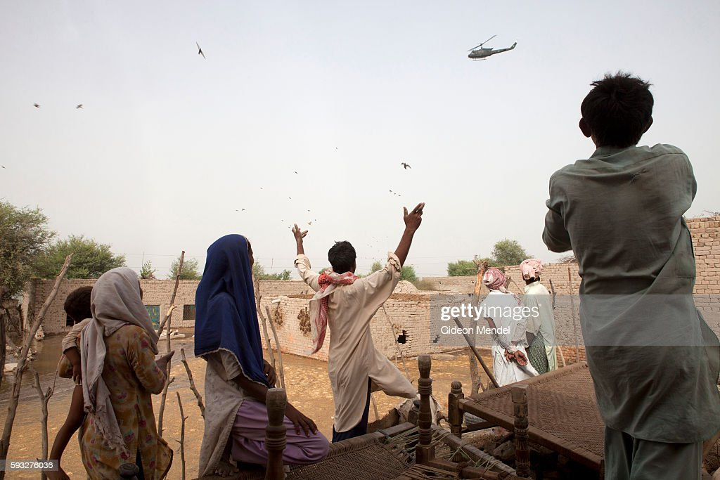 Residents of Rab Dino Ghambir village respond anxiously as an army helicopter drops some food parcels into their village which had just been stranded...