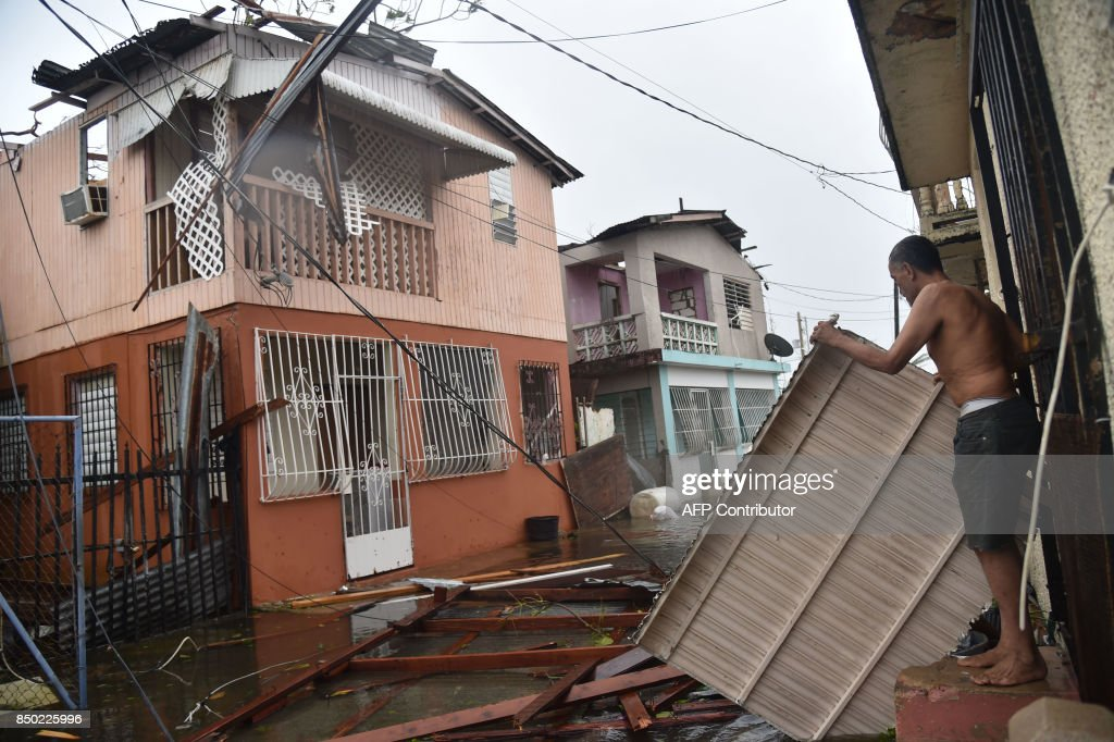 Residents of San Juan, Puerto Rico, deal with damages to their homes on September 20, 2017, as Hurricane Maria batters the island. Maria slammed into Puerto Rico on Wednesday, cutting power on most of the US territory as terrified residents hunkered down in the face of the island's worst storm in living memory. After leaving a deadly trail of destruction on a string of smaller Caribbean islands, Maria made landfall on Puerto Rico's southeast coast around daybreak, packing winds of around 150mph (240kph). PHOTO / Hector RETAMAL