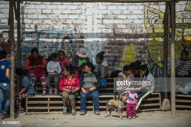 Residents of San Pablo Mirador community Chancay district in the outskirts of Lima attend a football match with former French world football champion...