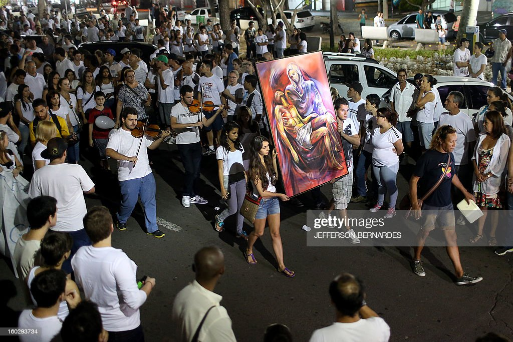Residents of Santa Maria march along the Rio Branco avenue demanding justice and in homage to the Kiss nightclub fire victims on January 28, 2013, in Santa Maria, southern Brazil, where a blaze on the eve killed more than 230 people. Brazilian police arrested four suspects --two of the Kiss club's owners, along with a pair of musicians who starred in the ill-fated pyrotechnic show, in the wake of the nightclub fire that forced sports officials to defend preparations for the World Cup and Olympics. AFP PHOTO / JEFFERSON BERNARDES