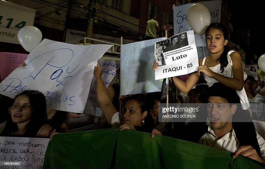 Residents of Santa Maria march along the Rio Branco avenue demanding justice and in homage to the victims of the Kiss nightclub fire on January 28, 2013, in Santa Maria, southern Brazil, where a blaze on the eve killed more than 230 people. Brazilian police arrested four suspects --two of the Kiss club's owners, along with a pair of musicians who starred in the ill-fated pyrotechnic show, in the wake of the nightclub fire that forced sports officials to defend preparations for the World Cup and Olympics.