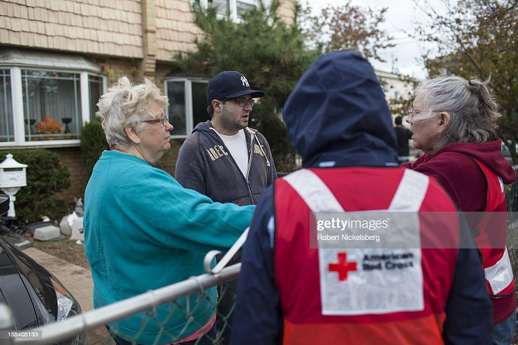 Residents of Staten Island speak with American Red Cross representatives November 3, 2012 in Midland Beach after Superstorm Sandy left millions without power or water in the Staten Island borough of New York. The storm continues to affect business and daily life throughout much of the eastern seaboard.