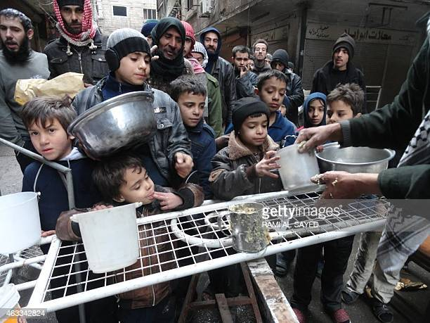 Residents of Syria's besieged Yarmuk Palestinian refugee camp south of Damascus gather to collect aid food at the adjacent Jazira neighborhood on...