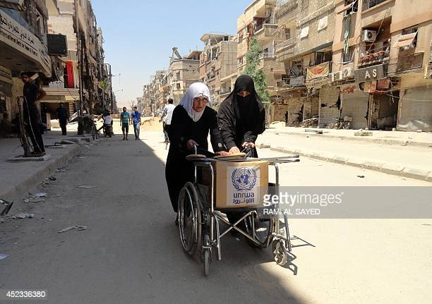 Residents of Syria's Yarmuk Palestinian refugee camp south of Damascus use a wheelchair to carry a box of goods distributed by the United Nations...