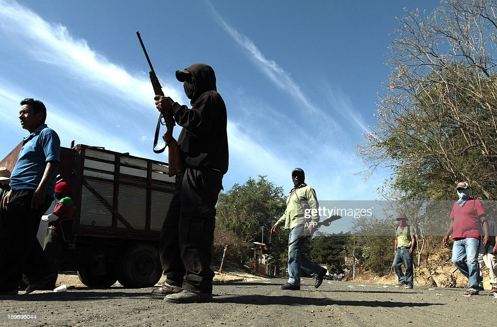 Residents of Tecoanapa, in the Mexican southern state of Guerrero, forming their own vigilante police forces, stand guard at a checkpoint in the main access to the nearby village of Pericon on January 18, 2013. Hundreds of civilians armed with rifles, pistols and machetes decided to provide security for the communities of Tecoanapa and Ayutla de los Libre in the state of Guerrero, saying gangs were committing robberies, kidnappings and murder. The vigilante force has put up checkpoints on roads and conducts night watches in the towns. Guerrero, home to the Pacific resort town of Acapulco, has been one of the states hardest hit by Mexico's drug violence, which has left more than 70,000 people killed across the country since 2006. AFP PHOTO/Pedro Pardo