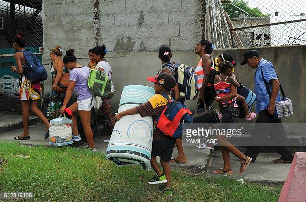 TOPSHOT Residents of the Cuban community of Cecilia in Guantanamo Province are evacuated on October 3 2016 as Hurricane Matthew claimed its first two...