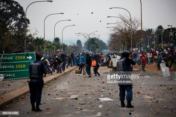 Residents of the Eldorado Park and Freedom Park districts throw stones during clashes with riot police in Johannesburg on May 8 2017 following a...