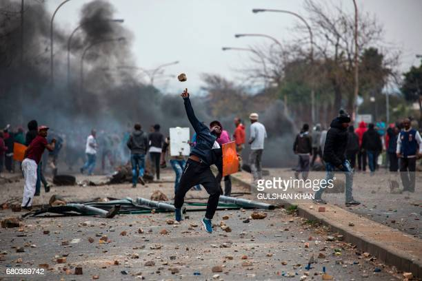 TOPSHOT Residents of the Eldorado Park and Freedom Park districts throw stones during clashes with riot police in Johannesburg on May 8 2017...