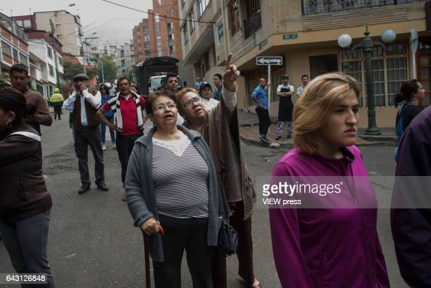 Residents of the neighborhood gather to observe the scene after a bomb exploded in the Macarena neighborhood behind the La Santamaría bullfighting...