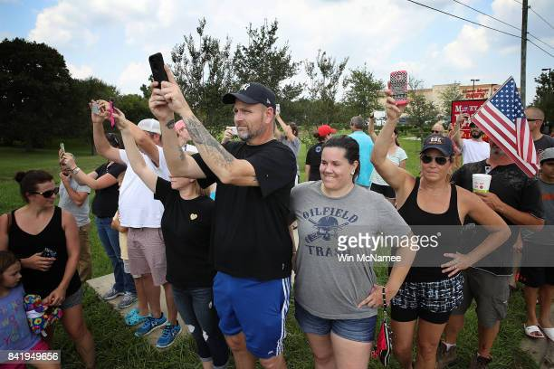 Residents of the Pearland Texas area watch as US President Donald Trump's motorcade leaves the First Church of Pearland September 2 2017 in Pearland...
