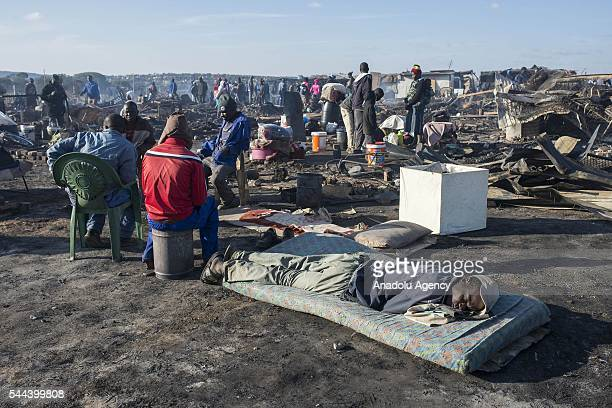 Residents of the Plastic View informal settlement collects usable household goods after a huge fire destroyed over 200 homes in the slum area east of...