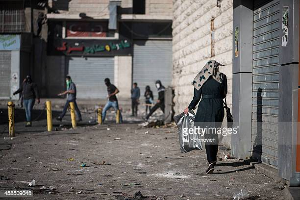 residents of the refugee camp seen passing as palestinian youth clash with police at Shuafat refugee camp a day after a Palestinian resident of the...