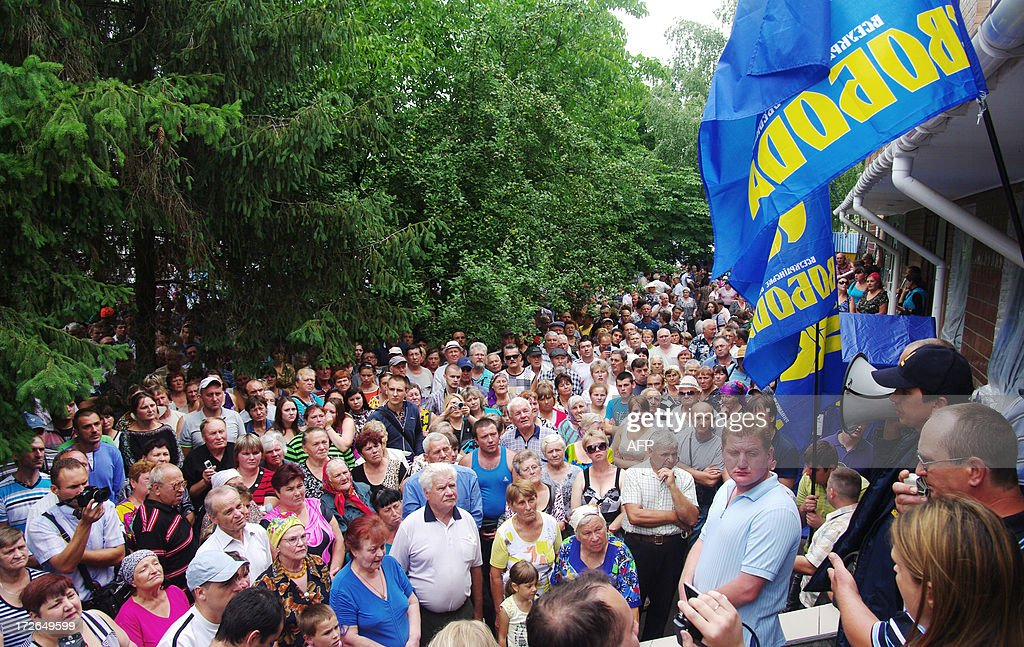 Residents of the small Ukrainian ciry of Vradiyivka, in Ukraine's Mykolayiv region, protest outside of the police station on July 4, 2013. Several hundred protesters stormed a police station in southern Ukraine on July 2 after authorities initially failed to arrest one of two policemen implicated in the brutal rape of a young woman. The huge outrage prompted Ukraine's President Viktor Yanukovych to order a top-level enquiry into the gang rape of 29-year-old Iryna Krashkova. AFP PHOTO/ ALEXEY KRAVTSOV