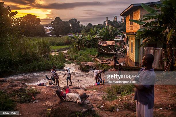 Residents of the town of Kailahun gather along a river at dusk on Tuesday August 19 2014