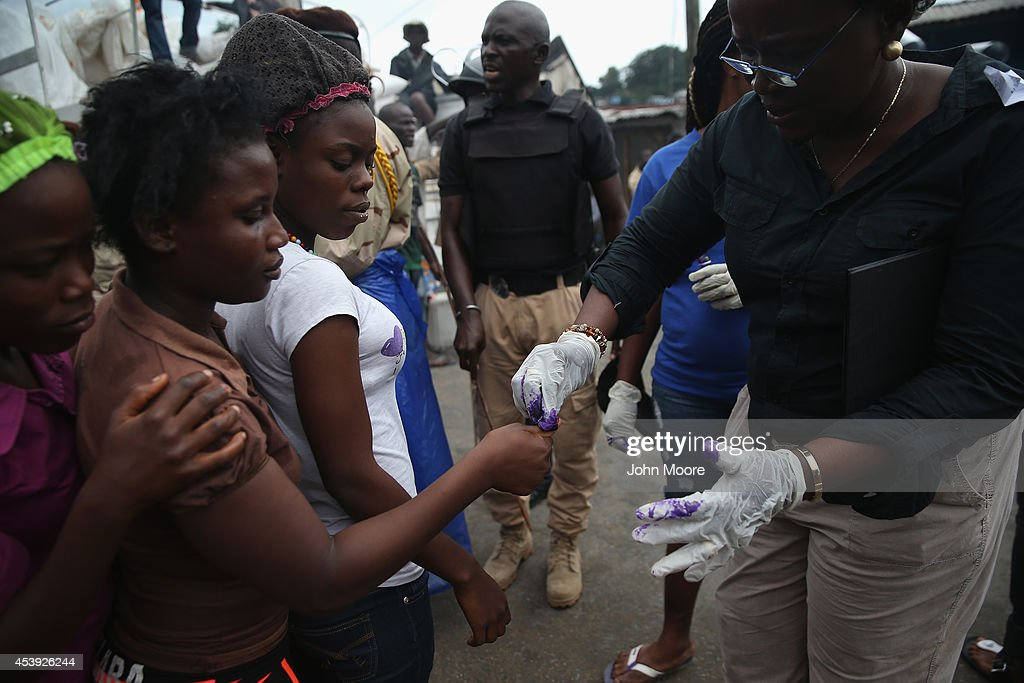 Residents of the West Point slum are marked with ink just before receiving food aid during the second day of the government's Ebola quarantine on...