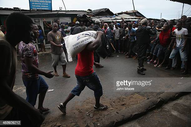 Residents of the West Point slum receive food aid during the second day of the government's Ebola quarantine on their neighborhood on August 21 2014...