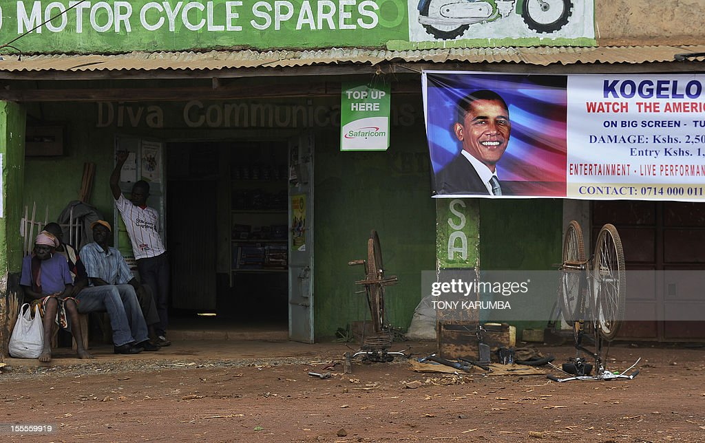 Residents of the western Kenyan hamlet of Kogelo sit on November 5, 2012 near a banner, bearing the picture of incumbent US President Barack Obama, a day from what many of the residents hope will be his re-election to a second term. Obama's father was born in Kogelo. AFP PHOTO/Tony KARUMBA