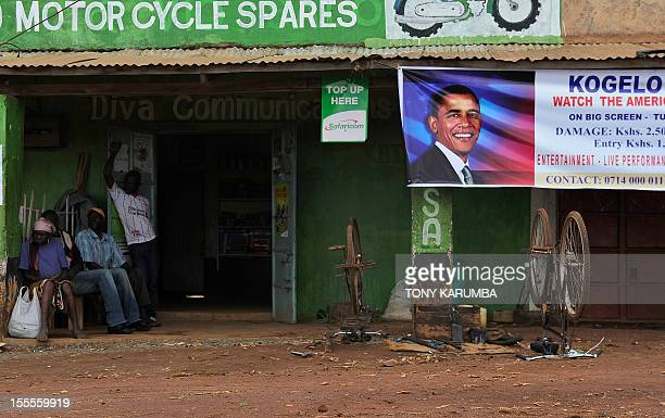 Residents of the western Kenyan hamlet of Kogelo sit on November 5 2012 near a banner bearing the picture of incumbent US President Barack Obama a...