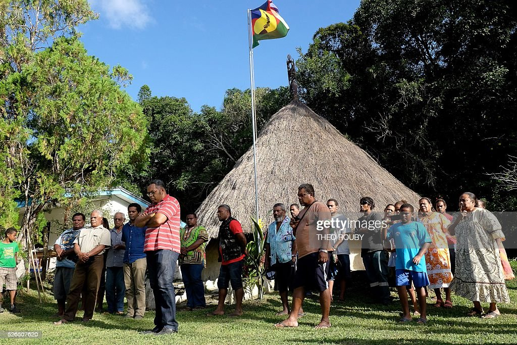 Residents of Tiendanite stand with Emmanuel Tjibaou (6th L), son of Kanak independentist leader Jean-Marie Tjibaou, as they greet the French prime minister on April 30, 2016 in Tiendanite, near Hienghene, as part of his visit to the French Pacific territory of New Caledonia. / AFP / Th��o Rouby