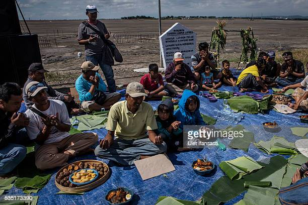 Residents of villages pray together at mudflow during the tenth anniversary of the mudflow eruption on May 29 2016 in Sidoarjo East Java Indonesia On...