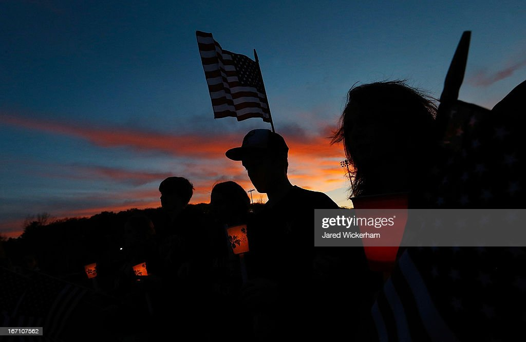 Residents of Watertown stand during a moment of silence at a candlelight vigil at Victory Park on April 20 2013 in Watertown Massachusetts A manhunt...