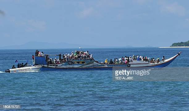 Residents on board a wooden boat and escorted by Philippine maritime police arrive from the village of Mangpang at the sea wall to escape fresh...