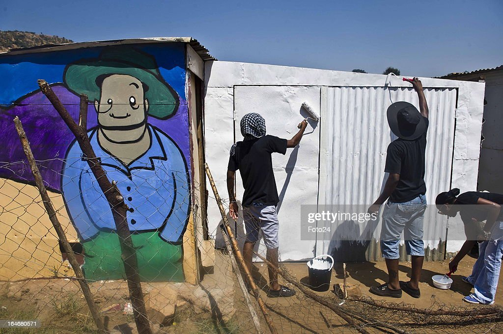 Residents paint a shack at the Alaska Informal settlement on March 24, 2013 in Mamelodi, South Africa. The Viva Foundation hosted the second Mams Art Festival at the informal settlement over the weekend. The art festival focuses on creating the world's first living art gallery by transforming shacks into art work.
