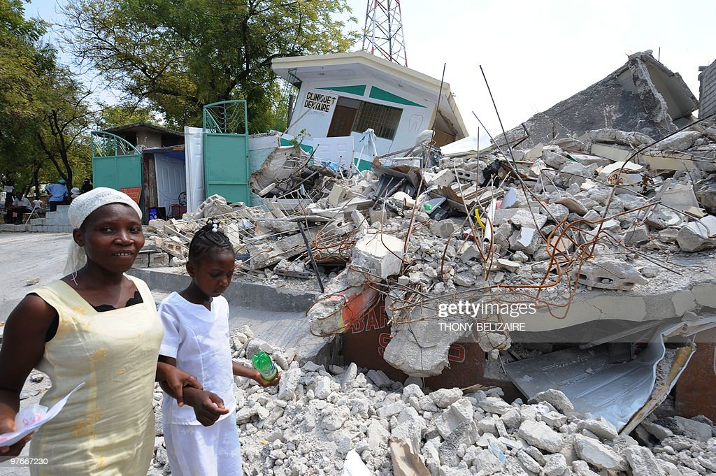 Residents pass the remains of a dental clinic on March 2010 in PortauPrince Two months after Haiti's January 12 earthquake aids groups were still...