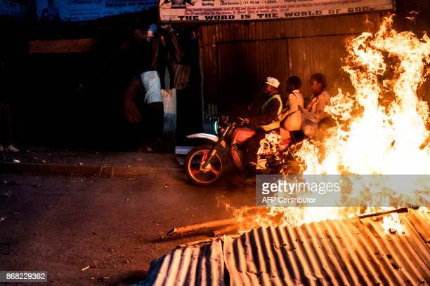 Residents pass through a burning barricade in the Mathare slums in Nairobi on October 30 during demonstrations following the announcements of the...