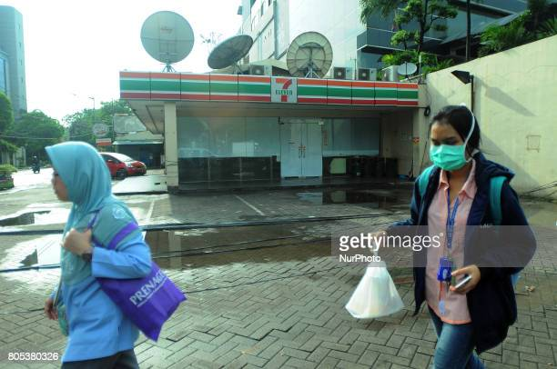 residents passing in front of 7 Eleven retail outlets are broke in glass cover with plastic and paper in Jakarta Indonesia on June 302017 The...