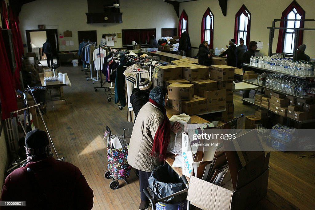 Residents pick-up items at a church which has been turned into a relief supply center following Hurricane Sandy in the Rockaways on January 25, 2013 in New York City. Three months after Sandy devastated parts of New York and New Jersey, hundreds of residents are still without electricity and heat and depend on churches and charities to meet their basic needs. This past week saw some of the coldest temperatures of the Winter hit parts of New York.