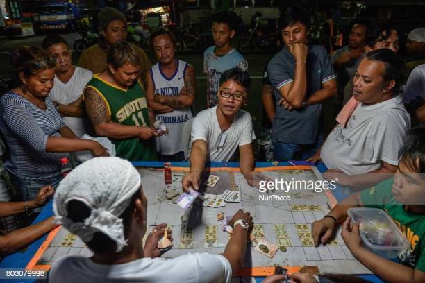 Residents place bets on a card game during the funeral wake of a victim of a drugrelated killing in Caloocan north of Manila Philippines March 30...
