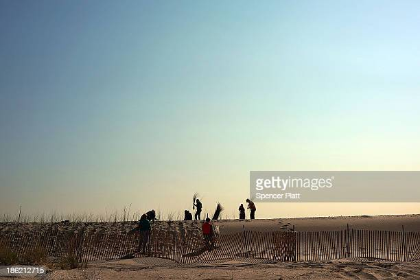 Residents plant beach grass on protective sand dunes in the Breezy Point neighborhood on the oneyear anniversary of Hurricane Sandy on October 29...