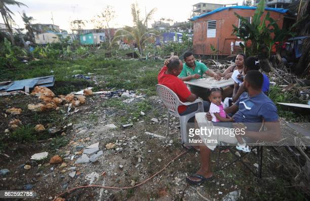 Residents play dominoes near their damaged homes after US soldiers unloaded food and water provided by FEMA to residents in the neighborhood still...