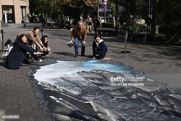 Residents pose for a picture with a 3D optical illusion artwork of a devastated cityscape in Aleppo Syria at the campus of the Meiji University in...