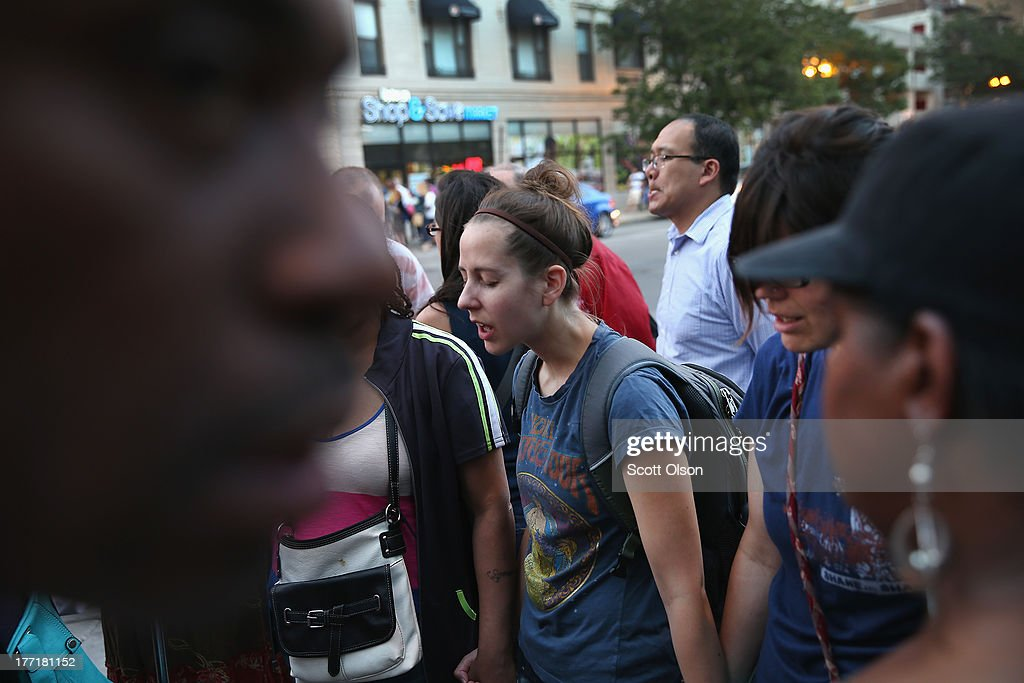 Residents pray outside the Uptown Baptist Church during a vigil for for the people wounded in Monday's shooting on August 21, 2013 in Chicago, Illinois. Five people who were standing in front of the church were shot August 19, when a gunman opened fire from a passing vehicle.