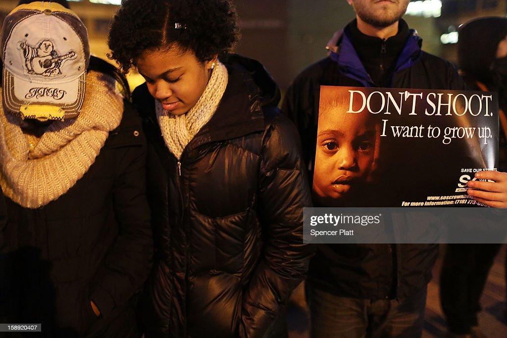 Residents pray while attending a rally and vigil on the sidewalk near where two teens were shot on New Year's Day on January 03, 2013 in the Crown Heights neighborhood of the Brooklyn borough of New York City. The gathering was sponsored by the local community group Save Our Streets Crown Heights (S.O.S.) which is a community-based effort to end gun violence. S.O.S. holds the gatherings at all shooting locations in Crown Heights to draw attention to the violence and to encourage a community response to the shootings. While murders were down for 2012 in New York City, robberies, burglaries and felony assaults rose.