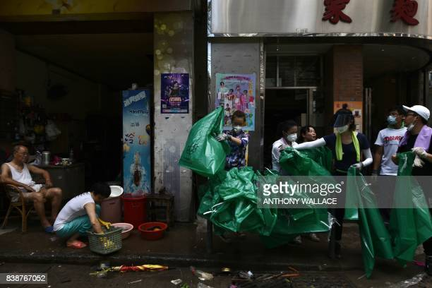 TOPSHOT Residents prepare rubbish bags as they help Chinese People's Liberation Army soldiers clear debris from a street in Macau on August 25 two...