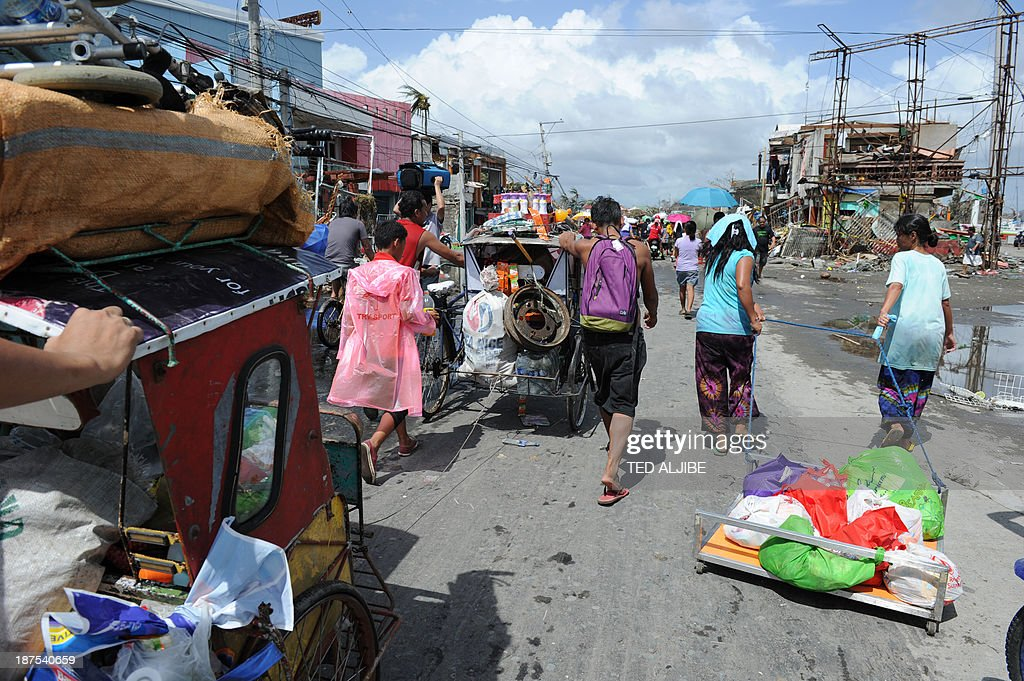 Residents pull an improvised trolley loaded with looted items in Tacloban, Leyte province, central Philippines on November 10, 2013, three days after devastating Typhoon Haiyan hit the city on November 8. The death toll from a super typhoon that decimated entire towns in the Philippines could soar well over 10,000, authorities warned on November 10, making it the country's worst recorded natural disaster.