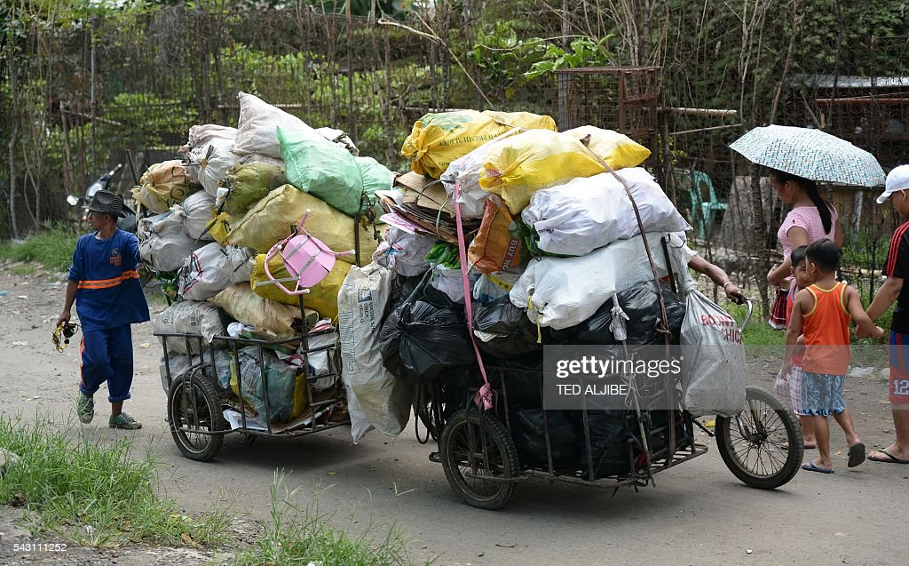 Residents push a tricycle loaded with recyclable materials to be sold at a junk shop near the former dumpsite and landfill named 'Smokey Mountain' in Manila on June 26, 2016. Incoming Philippine president Rodrigo Duterte pledged on May 26 to spread economic activity beyond the overpopulated capital of Manila, calling it a 'dead' city overrun by shantytowns. / AFP / TED