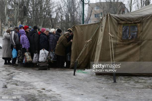Residents queue outside a tent to get warm clothes recived as humanitarian aid in Avdiivka Donetsk region on February 5 2017 Fighting subsided around...