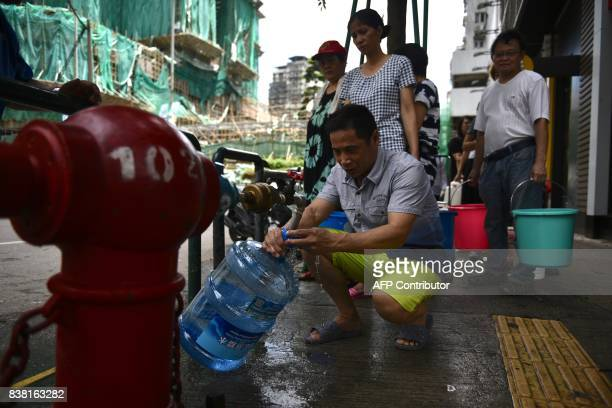 Residents queue up for water from a fire hydrant on a pavement in Macau on August 24 a day after Typhoon Hato hit the city causing power outages and...
