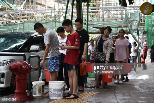 Residents queue up to collect water from a fire hydrant in Macau on August 24 a day after Typhoon Hato hit The death toll from Severe Typhoon Hato...