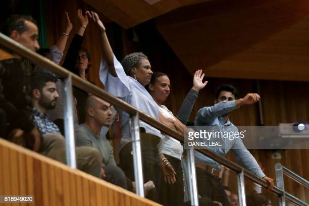 Residents raise their hands in rejection of Kensington and Chelsea Council's leader Elizabeth Campbell as she speaks during a council meeting to...
