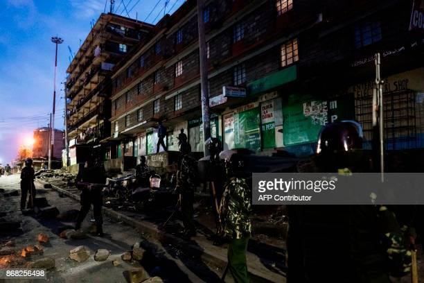 Residents raise their hands passing near deployed policemen while protesters gather around a burning barricade in the Mathare slums in Nairobi on...
