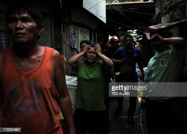 Residents react as fire engulfs a shanty town at the financial district of Manila on July 11 leaving more than 1000 people homeless according to city...