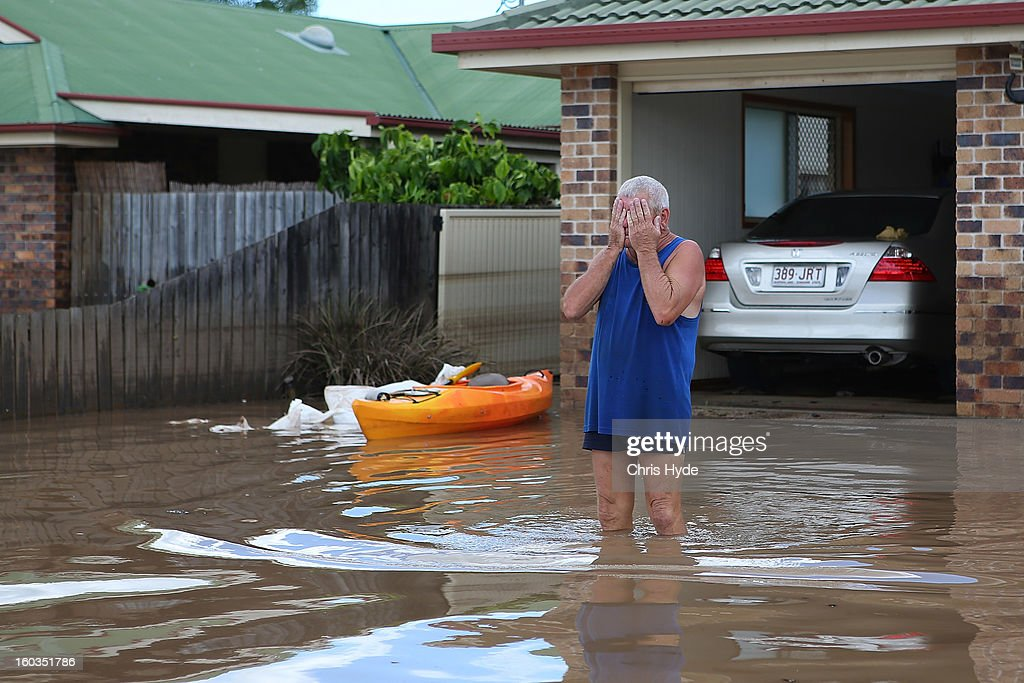 A residents reacts to the damage to his house as parts of southern Queensland experiences record flooding in the wake of Tropical Cyclone Oswald on January 30, 2013 in Bundaberg, Australia. Flood waters peaked at 9.53 metres in Bundaberg yesterday and began receding overnight, as residents and relief teams prepare to clean-up debris. Four deaths have been confirmed in the Queensland floods and the search is on for two men though to be missing in floodaters in Gatton.