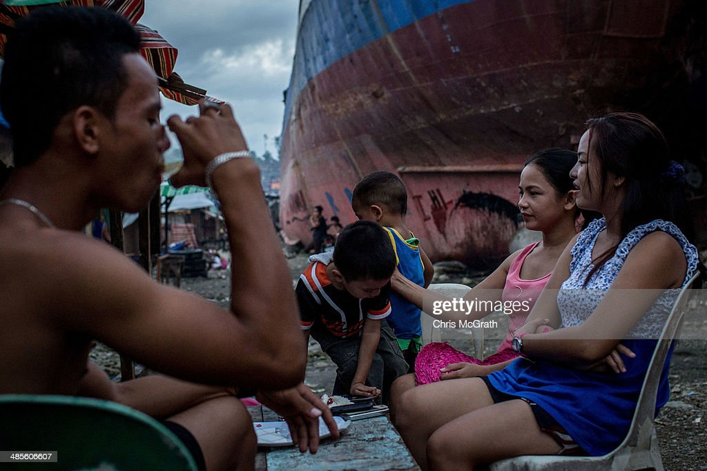 Residents relax and drink beer outside in the coastal area renamed by residents ' Yolanda Village' on April 19, 2014 in Tacloban, Leyte, Philippines. People continue to rebuild their lives five months after Typhoon Haiyan struck the coast on November 8, 2013, leaving more than 6000 dead and many more homeless. Although many businesses and services are functioning, electricity and housing continue to be the main issues, with many residents still living in temporary housing conditions due to 'No Build' areas preventing them from rebuilding their homes. This week marks Holy Week across the Philippines and will see many people attending religious activities.
